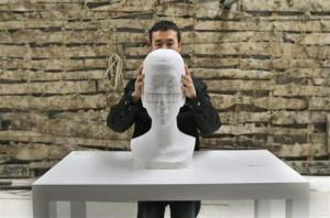 Source: Reuters. Image: Chinese artist Li Hongbo shows his paper sculpture work, made of 6,000 pieces of paper, while raising it at his studio on the outskirts of Beijing, January 20, 2014.  CREDIT: REUTERS/JASON LEE.