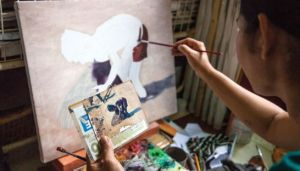 Source: The Phnom Penh Post. Image: Artist Venn Savat's wife works on a painting in their apartment. Charlotte Pert.